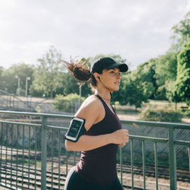 Confident sportswoman listening music through in-ear headphones while jogging on bridge in city